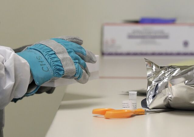 Pharmacist Michael Witte wears heavy gloves as he opens a frozen package of the potential vaccine for COVID-19, the disease caused by the new coronavirus, on the first day of a first-stage safety study clinical trial, Monday, March 16, 2020