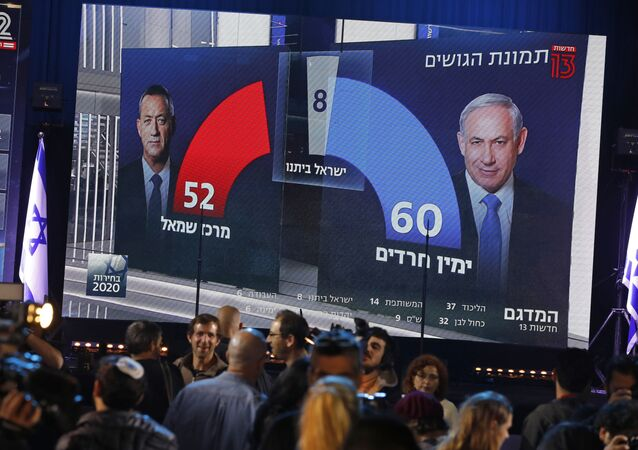 This picture taken on March 2, 2020 shows people standing before a giant screen displaying a broadcast from Israel's Channel 13 with an exit poll prediction after polls closed in the Israeli elections, predicting that Prime Minister Benjamin Netanyahu's Likud party expects to command a 60 seat bloc against 52 for Benny Gantz' Blue and White (Kahol Lavan) electoral alliance, at the Blue and White's headquarters in the coastal city of Tel Aviv.