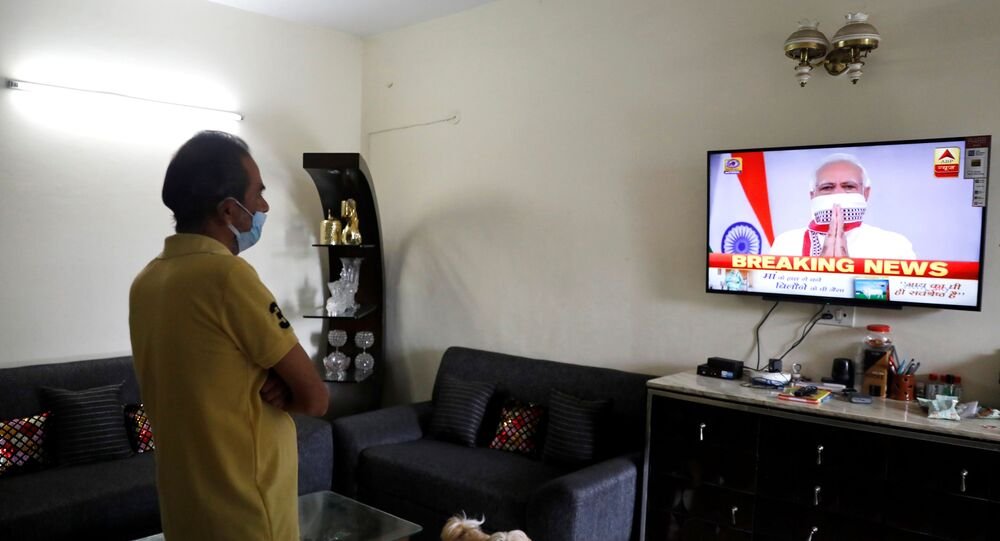A man watches India's Prime Minister Narendra Modi's address to the nation on a television announcing the extension of a nationwide lockdown till May 3, to limit the spreading of coronavirus disease (COVID-19), in in New Delhi, India, April 14, 2020. REUTERS/Anushree Fadnavis