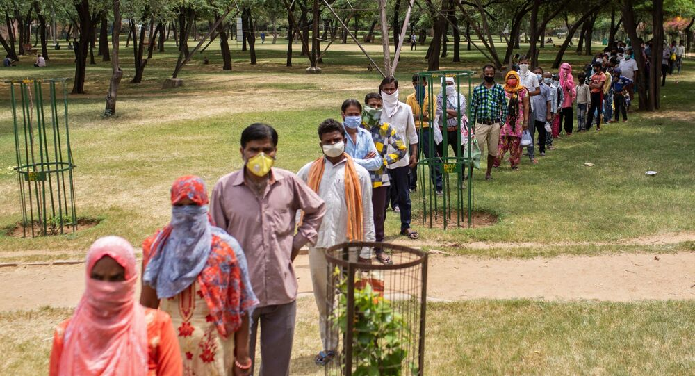 Residents stand in a queue for free food by government, during a nationwide lockdown to slow the spreading of the coronavirus disease (COVID-19), at a school in New Delhi, India, April 14, 2020