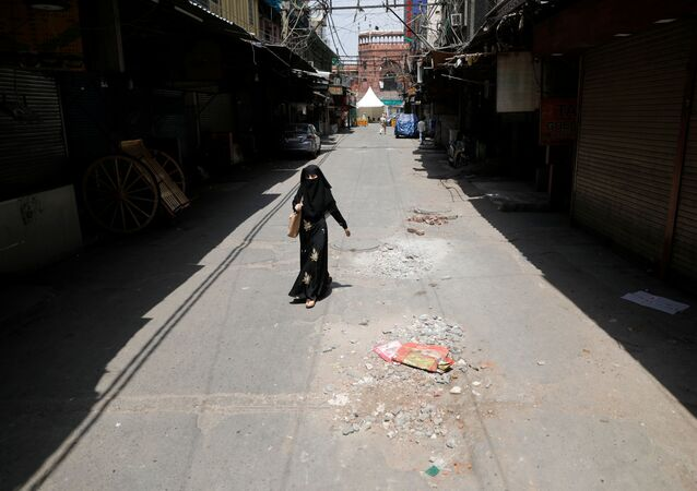 A woman walks on a deserted street during a nationwide lockdown to slow the spreading of the coronavirus disease (COVID-19) in the old quarters of Delhi, India, April 13, 2020