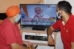 Residents wearing a facemasks watch on television Prime Minister Narendra Modi's address to the nation during a government-imposed nationwide lockdown as a preventive measure against the COVID-19 coronavirus, in Amritsar on April 14, 2020