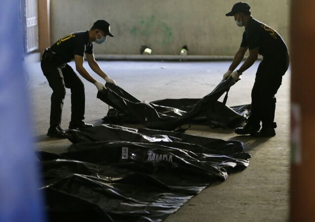 Members of Scene of the Crime Operatives of the Philippine National Police line up body bags (File)