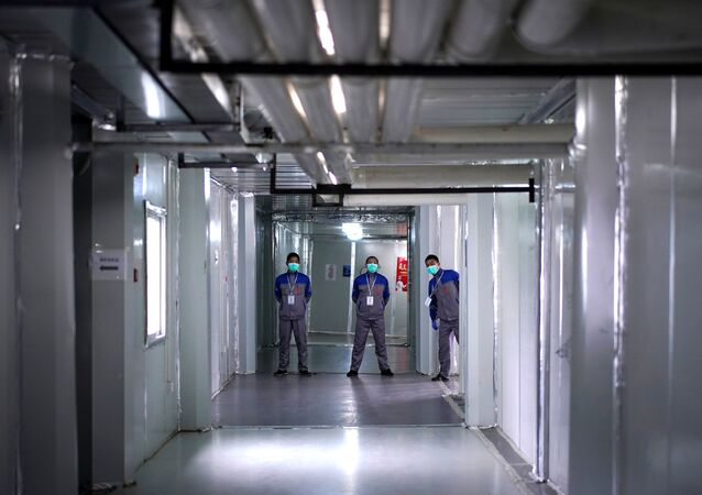 Security guards wearing face masks are seen near closed wards inside the Leishenshan Hospital, a makeshift hospital for treating patients with the coronavirus disease (COVID-19), in Wuhan, Hubei province, China April 11, 2020