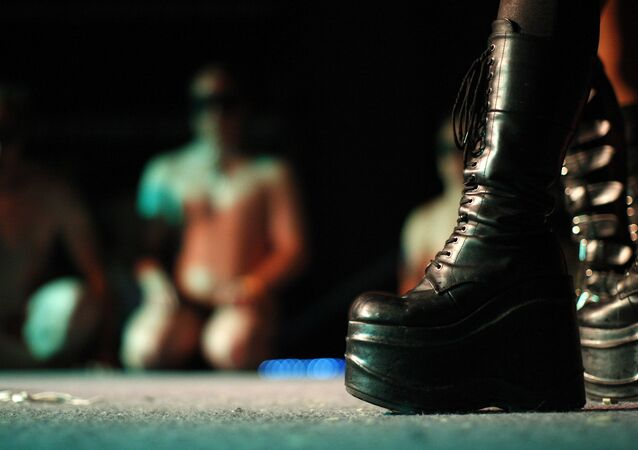 The boots of a dominatrix are seen as a naked man kneels in a BDSM convention in Los Angeles