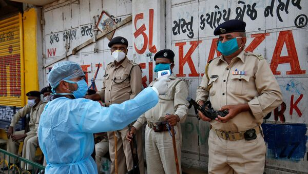 A paramedic uses an infrared thermometer to measure the temperature of a police officer alongside a road during a 21-day nationwide lockdown to slow the spreading of coronavirus disease (COVID-19) in Ahmedabad, India, 9 April 2020.  - Sputnik International