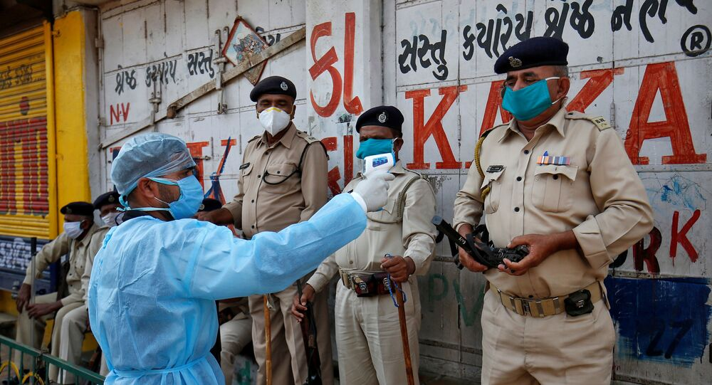 A paramedic uses an infrared thermometer to measure the temperature of a police officer alongside a road during a 21-day nationwide lockdown to slow the spreading of coronavirus disease (COVID-19) in Ahmedabad, India, 9 April 2020.
