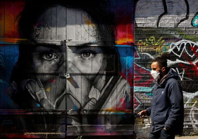 A man wearing a mask walks in Brick Lane in front of graffiti as the spread of the coronavirus disease (COVID-19) continues, London, Britain, April 14, 2020