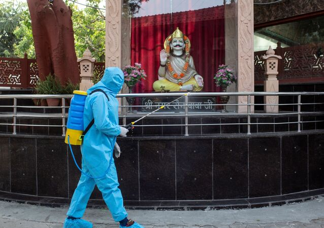 A health worker wearing protective gear sprays disinfectant at a crematorium to slow the spreading of the coronavirus disease (COVID-19), after India extended a nationwide lockdown to contain the disease, in New Delhi, India, April 14, 2020.
