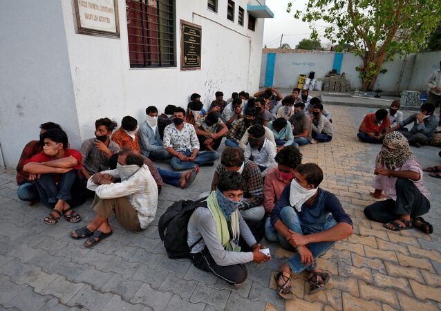 Migrant workers wait to be shifted to a shelter during a 21-day nationwide lockdown to slow the spreading of the coronavirus disease (COVID-19), in Ahmedabad, India, March 31, 2020.