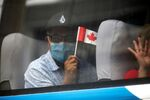 A man in a face mask waves a Canadian flag