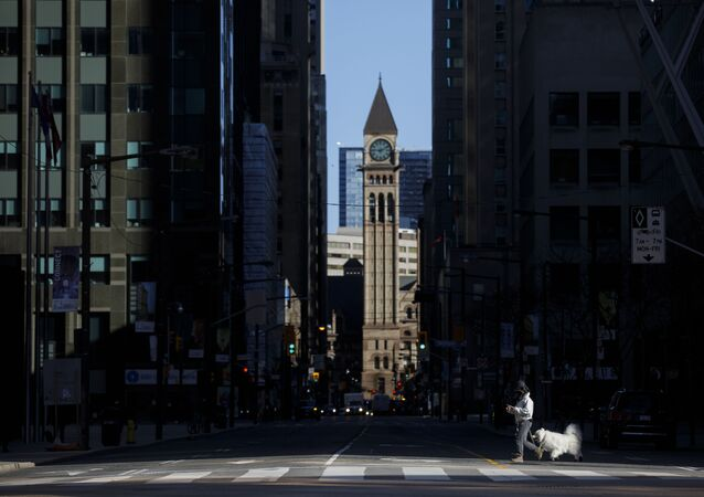 A pedestrian crosses the street with a dog during morning commuting hours in the Financial District as Toronto copes with a shutdown due to the Coronavirus, on April 1, 2020 in Toronto, Canada