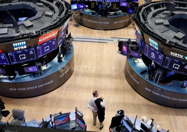 A trader puts on his jacket on the floor of the New York Stock Exchange (NYSE) as the building prepares to close indefinitely due to the coronavirus disease (COVID-19) outbreak in New York, U.S., March 20, 2020
