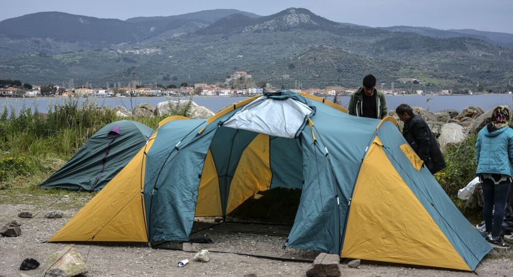 Migrants try to install a tent in the village of Petra on the northeastern Aegean island of Lesbos, Greece, Friday, 27 March 2020. Some 56 migrants who reached Lesbos in smugglers' boats from Turkey over the past few days have been quarantined in small tents in Petra for the past three days. Under public health measures adopted to hinder the spread of the new coronavirus, Greece places all people arriving from abroad in two-week quarantine. Lesbos' main migrant facility, near the village of Moria, is crammed with about 20,000 people even though it was built for 2,700.