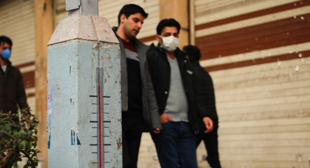 People wearing protective masks walk along a street in downtown Tehran, Iran.