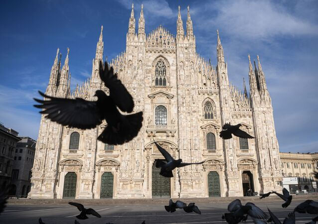 Pigeons fly over a deserted Piazza del Duomo in central Milan on 12 April 2020 during the country's lockdown aimed at curbing the spread of the COVID-19 infection, caused by the novel coronavirus.