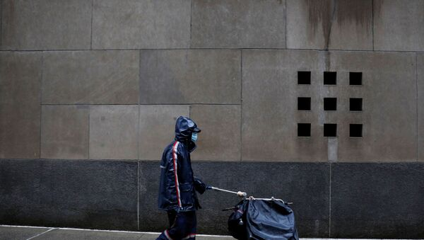 A United States Postal Service (USPS) worker works in the rain in Manhattan during the outbreak of the coronavirus disease (COVID-19) in New York City, New York, U.S., April 13, 2020 - Sputnik International