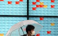 A man with a protective mask stands in the rain in front of an electronic stock board showing Japan's Nikkei 225 index at a securities firm in Tokyo Monday, April 13, 2020