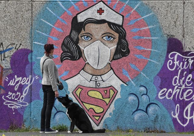 A woman watches a coronavirus graffiti by street artist 'Uzey' showing a nurse as Superwoman on a wall in Hamm, Germany, on Easter Monday, April 13, 2020