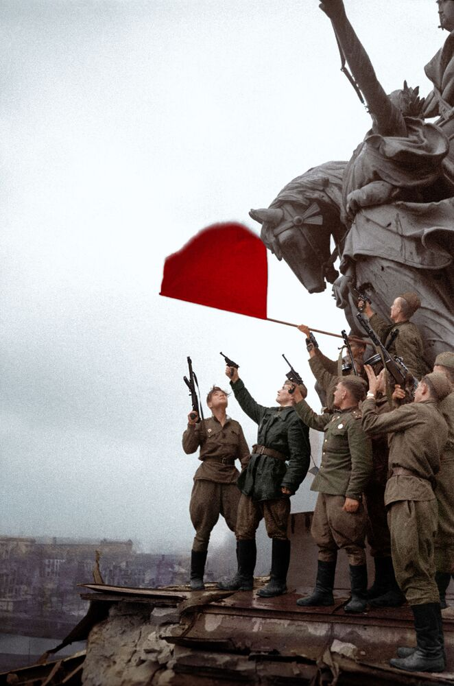 Soviet soldiers salute on the roof of the Reichstag.