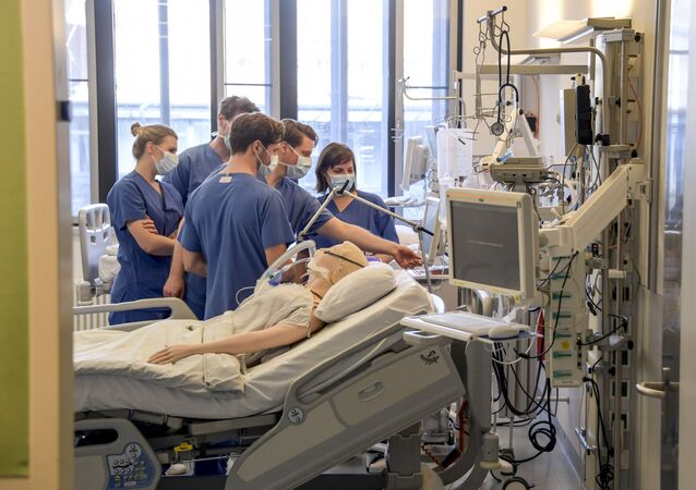 In this Tuesday, March 25, 2020, photo, hospital doctors get instructions on a ventilator at the University Hospital Eppendorf in Hamburg Germany