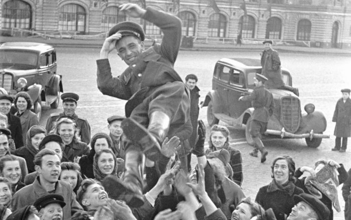 Muscovites are throwing an officer into the air as they celebrate Victory Day on 9 May 1945 on Red Square
