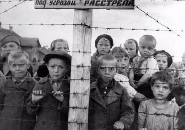 Staged photograph of Russian children at a formerly Finnish-run transfer camp in Petrozavodsk; photo taken by photographer Galina Sanko on 29 June 1944, one day after the Finns had left the area. The sign reads, in Finnish and Russian: Transfer camp. Entry to the camp and socializing through the fence are forbidden, violators will be shot