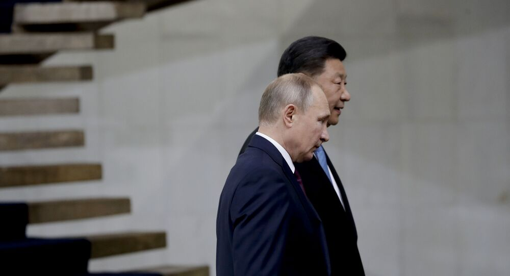 Russia's President Vladimir Putin and China's President Xi Jinping walk after the family photo of leaders of the BRICS emerging economies at the Itamaraty palace in Brasilia, Brazil, Thursday, Nov. 14, 2019