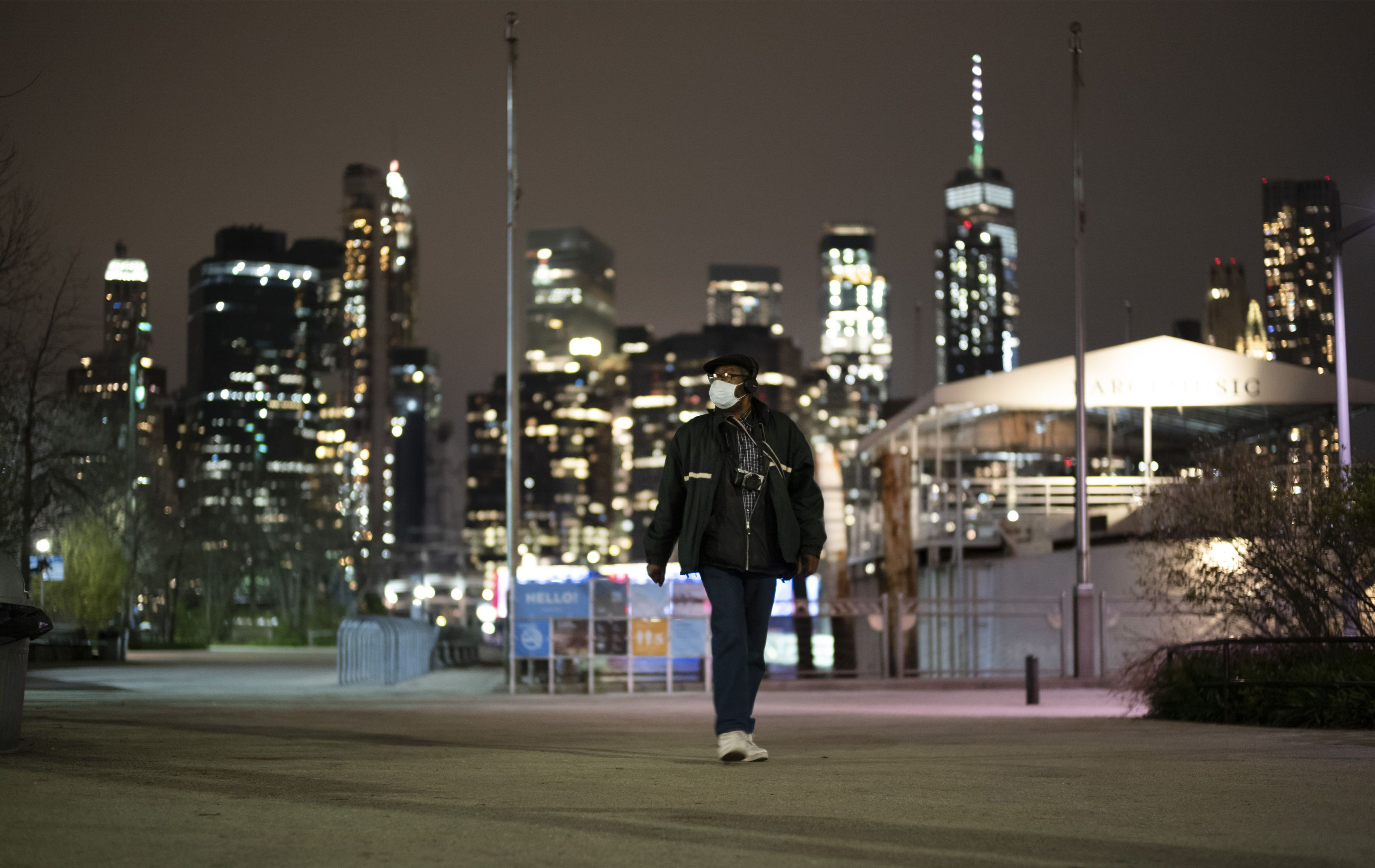 A man wearing a mask walks through Brooklyn Bridge Park, Tuesday night, April 14, 2020 during the coronavirus pandemic in New York. Known as The City That Never Sleeps, New York's streets are particularly empty during the pandemic.