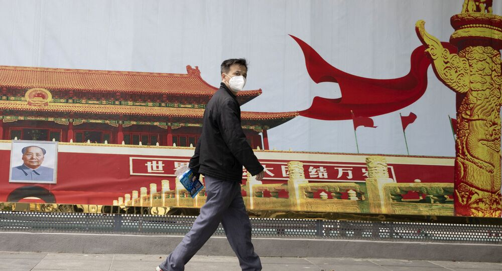 A resident wearing a mask against coronavirus walks past government propaganda poster featuring Tiananmen Gate in Wuhan in central China's Hubei province Thursday, April 16, 2020