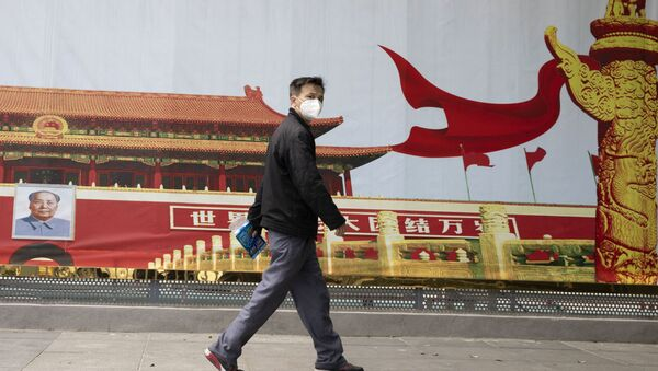 A resident wearing a mask against coronavirus walks past government propaganda poster featuring Tiananmen Gate in Wuhan in central China's Hubei province Thursday, April 16, 2020 - Sputnik International