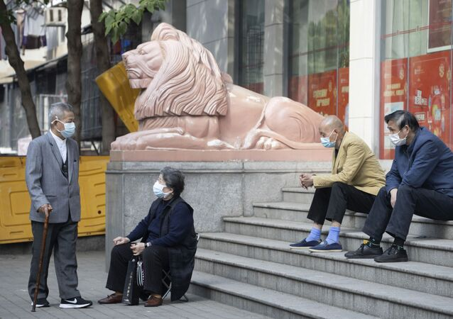 Elderly residents wearing masks against the coronavirus wait outside a bank in Wuhan in central China's Hubei province Thursday, April 16, 2020