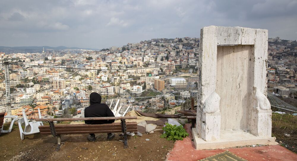 In this Tuesday, 4 Feb. 2020, photo, an Israeli Arab youth sits at a view point overlooking the Israeli Arab town of Umm al-Fahm. President Donald Trump's Mideast initiative suggests that a densely populated Arab region of Israel could be added to a future Palestinian state, if both sides agree. The proposal has infuriated many of Israel's Arab citizens, who view it as a form of forced transfer