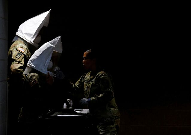 U.S. Army soldiers wear qualitative test fit hoods, filled with sweet or bitter solution to test if their N95 masks fit properly at a military field hospital for non-coronavirus patients inside CenturyLink Field Event Center during the coronavirus disease (COVID-19) outbreak in Seattle, Washington, U.S., April 1, 2020