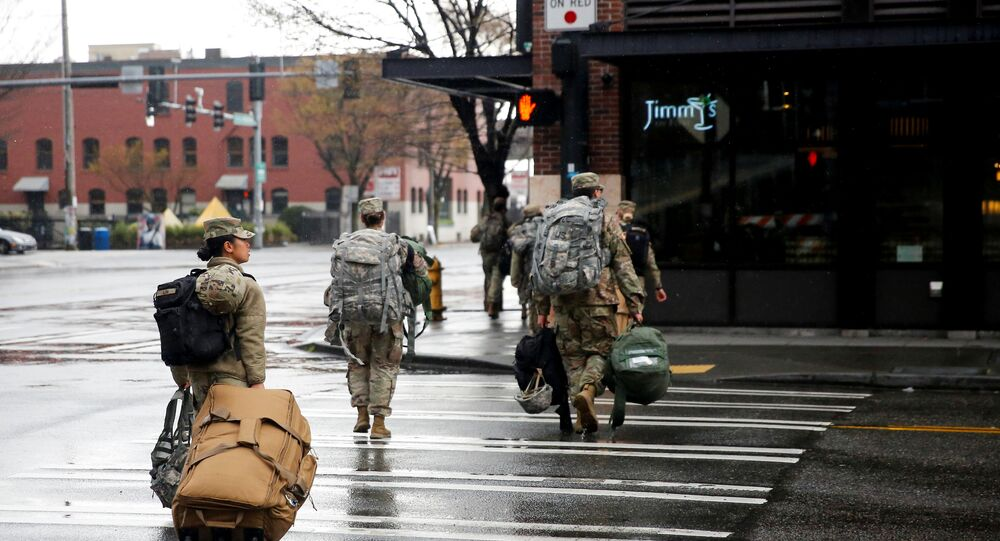 Soldiers from the 627th Army Hospital from Fort Carson, Colorado walk across the street after working at CenturyLink Field Event Center, which is being turned into a military field hospital for non coronavirus patients during the coronavirus disease (COVID-19) outbreak in Seattle, Washington, U.S. March 30, 2020