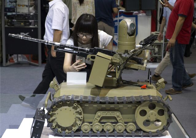A visitor takes a photo of a remote-controlled weaponized robot on display at the 8th China International Exhibition on Police Equipment in Beijing, China, Thursday, May 19, 2016