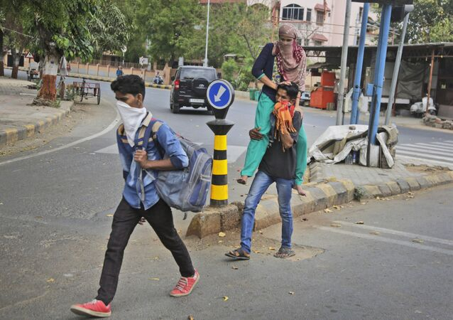 A migrant worker from neighboring state of Rajasthan carries her wife on his shoulder, as they leave for their village after the city comes under lock down as a precautionary measure against COVID-19 in Ahmedabad, India, Thursday, March 26, 2020