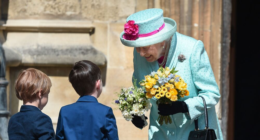 Britain's Queen Elizabeth II smiles as she receives posies of flowers from children after attending the Easter Mattins Service at St. George's Chapel, Windsor Castle on April 21, 2019.
