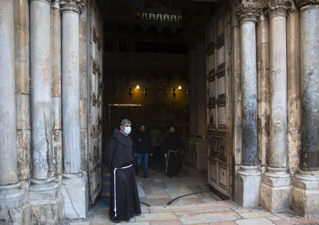 A Christian clergyman waits for the Easter Sunday Mass at the Church of the Holy Sepulchre, believed by many Christians to be the site of the crucifixion and burial of Jesus Christ, in Jerusalem's old city, Sunday, April 12, 2020.