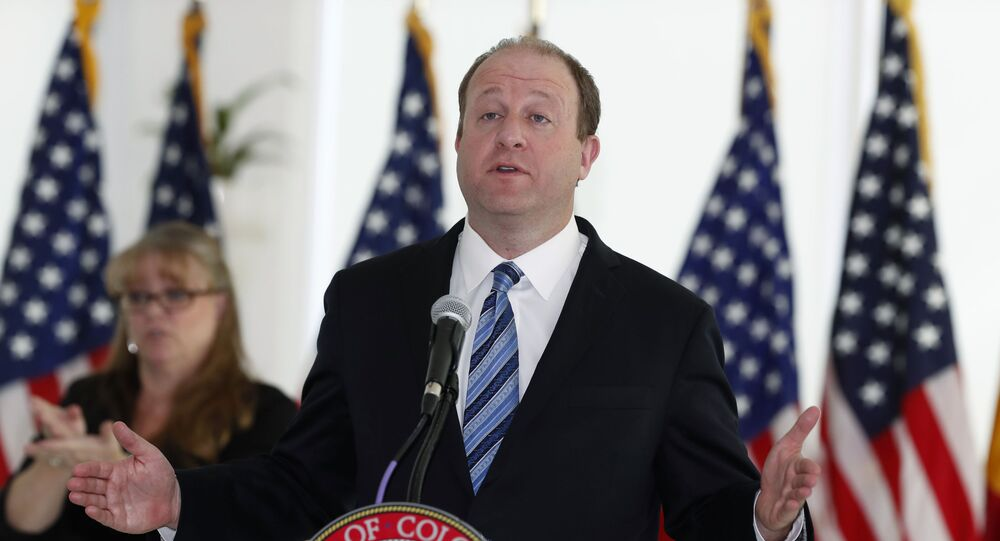 Colorado Governor Jared Polis makes a point during a news conference to update the state's efforts to control the spread of the new coronavirus Friday, April 17, 2020, at the governor's mansion in Denver.