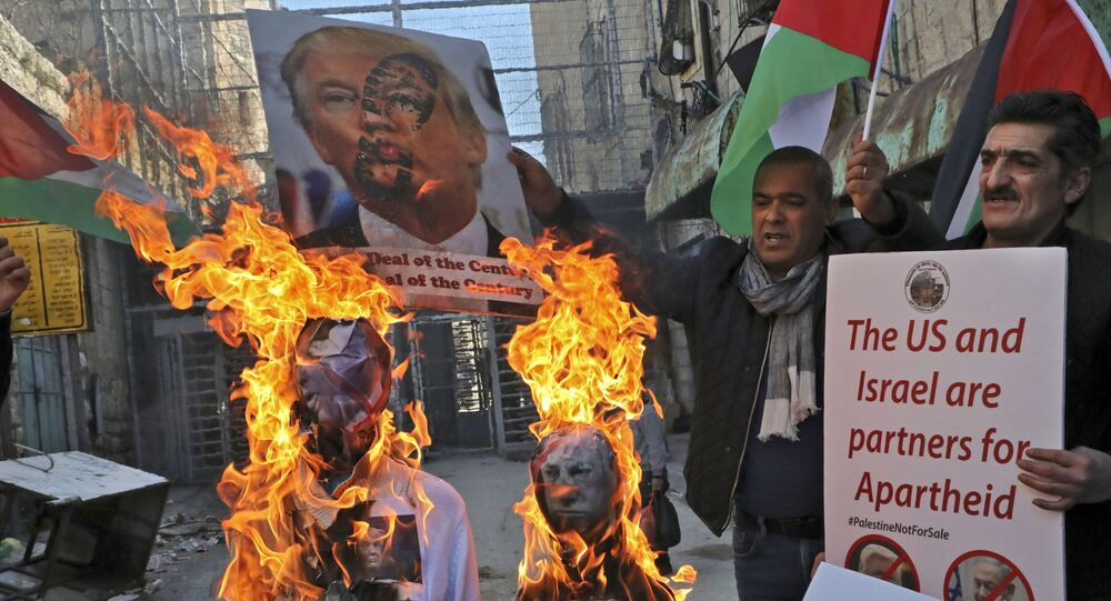 Demonstrators wave Palestinian flags as they burn effigies of US President Donald Trump and Israeli Prime Minister Benjamin Netanyahu during a protest against Trump's proposed Israeli-Palestinian peace plan, dubbed as the deal of the century, outside an Israeli checkpoint in the flashpoint city of Hebron in the occupied West Bank on February 28, 2020.