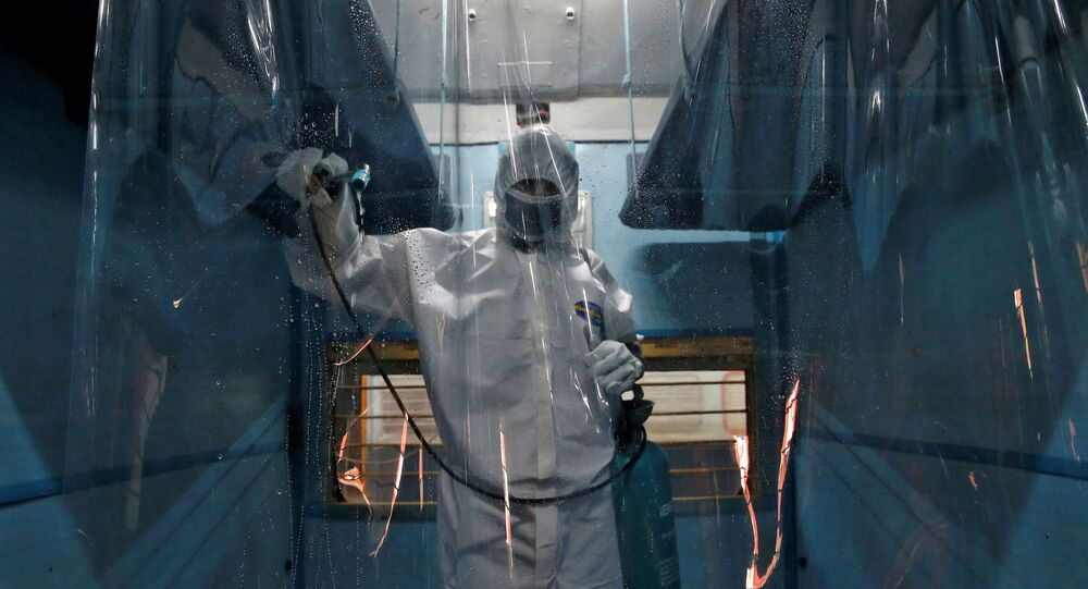 A worker wearing a protective suit disinfects the interior of a passenger train after it was converted into an isolation facility amid concerns about the spread of coronavirus disease (COVID-19), on the outskirts of Kolkata, India, April 6, 2020.