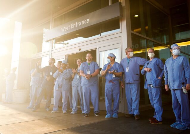 Healthcare workers clap as they are greeted by first responders from multiple cities during a shift change at the EvergreenHealth Medical Center, which saw the first death due to the coronavirus disease (COVID-19) in the U.S., and has treated hundreds of other cases, in Kirkland, Washington, U.S. April 16, 2020.