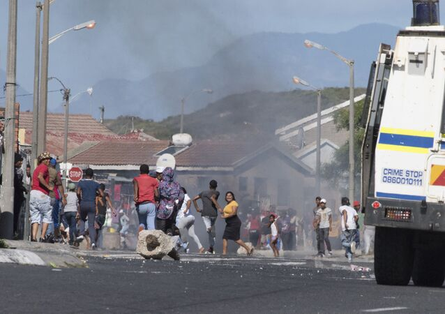 People run away as a South African Police Services armoured vehicle drives into a street during clashes with residents of Tafelsig, an impoverished suburb in Mitchells Plain, near Cape Town, on April 14, 2020, after some people in the community did not receive food parcels which were being handed out as part of the support for this community during the nation wide lockdown to curb the spread of the COVID-19 coronavirus.