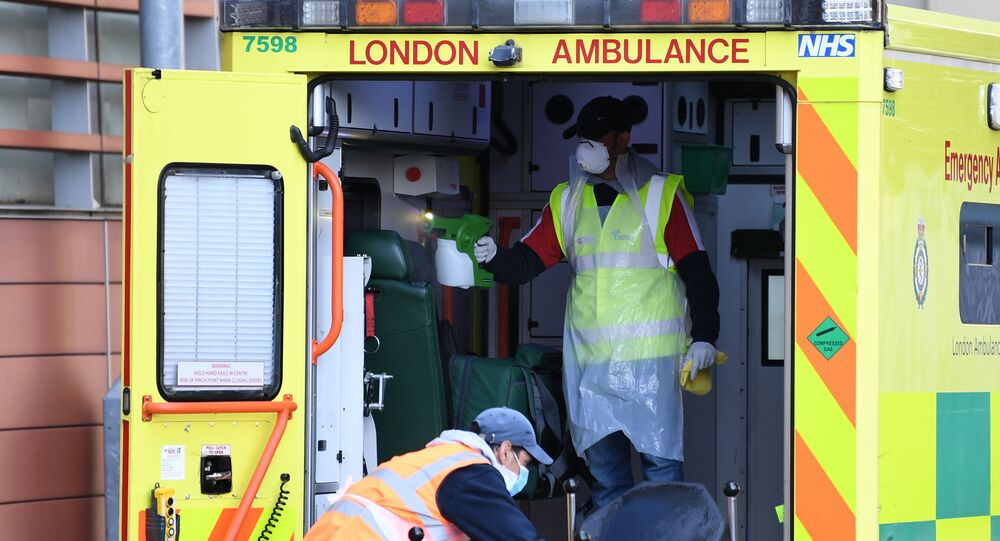 Staff wearing personal protective equipment (PPE) disinfect a London Ambulance outside The Royal London Hospital in east London on April 19, 2020.