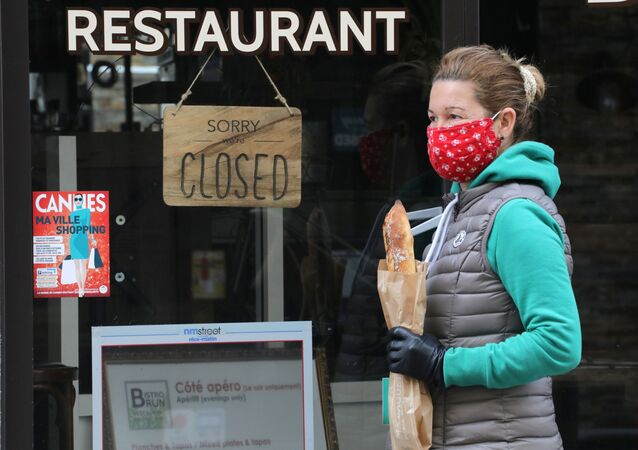 A woman wearing a protective face mask holds a French baguette as she walks past a closed restaurant in Cannes during a lockdown imposed to slow the rate of the coronavirus disease (COVID-19) in France, April 16, 2020