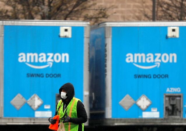 A worker in a face mask walks by trucks parked at an Amazon facility as the global coronavirus outbreak continued in Bethpage on Long Island in New York, U.S., March 17, 2020