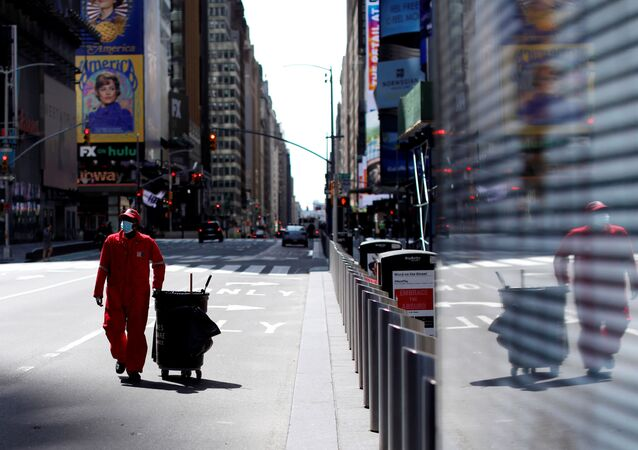 A Times Square Alliance street sweeper worker walks though a nearly empty Times Square in Manhattan during the outbreak of the coronavirus disease (COVID-19) in New York City, New York, U.S., April 7, 2020