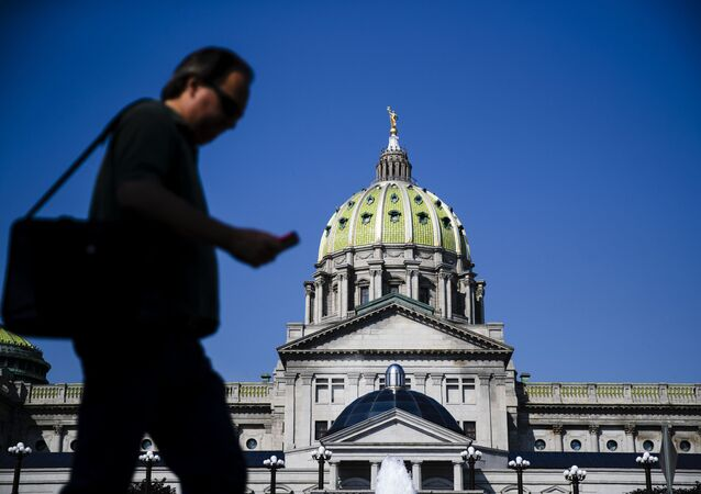 A pedestrian walks by the state Capitol in Harrisburg, Pa.,
