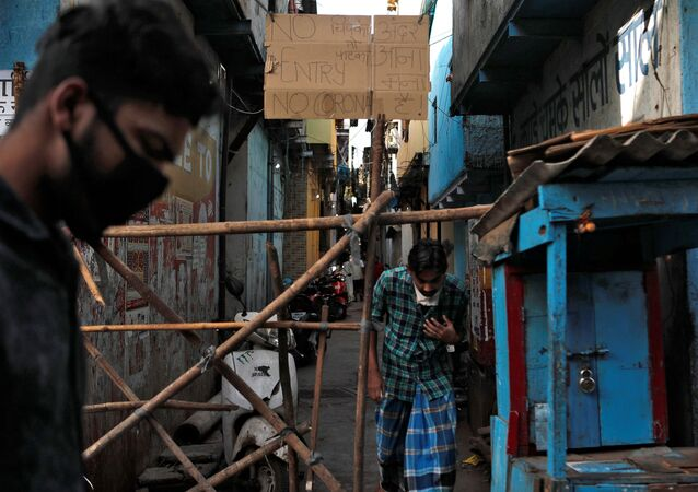 Men walk past a makeshift barricade that was set up to stop people from entering a lane, during a nationwide lockdown in India to slow the spread of COVID-19, in Dharavi, one of Asia's largest slums, during the coronavirus disease outbreak, in Mumbai, India, April 9, 2020